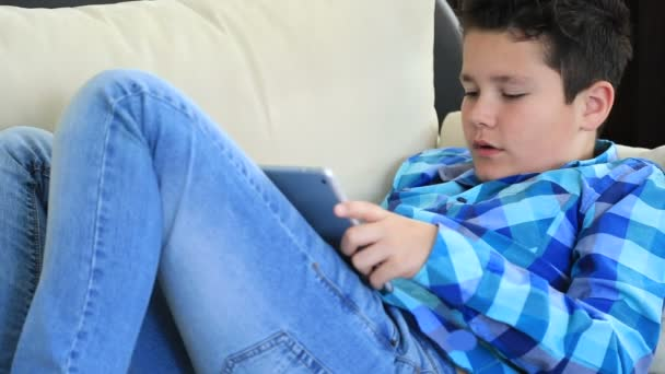 Portrait of a relaxed preteen boy laying sofa with digital tablet texting message or playing game at home. Technology, internet communication and people concept