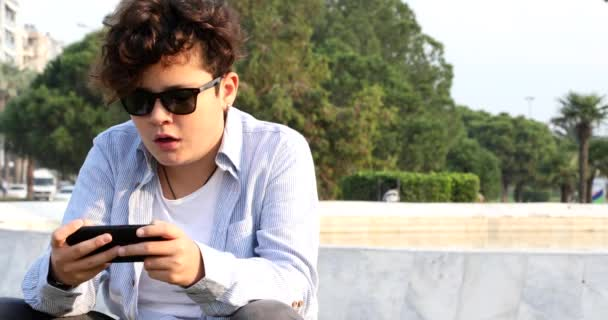 Portrait of a relaxed teenage boy sitting at the city park with smart phone. Kid watching to screen, reading, typing, playing games. Technology, internet communication and people concept, Smartphone addiction
