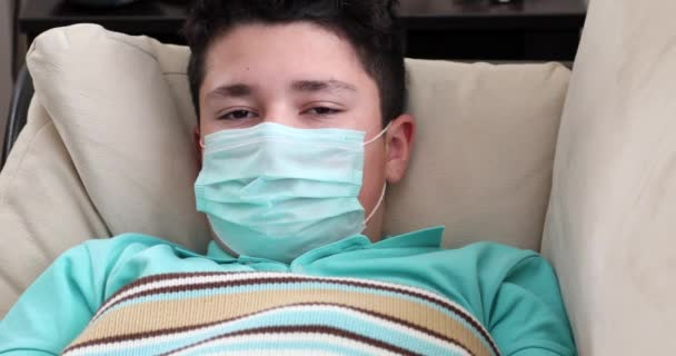 Portrait of a caucasion teenage boy in protective medical mask lying at home Virus Flu Pneumonia Coronavirus Covid 19 Epidemic Pandemic