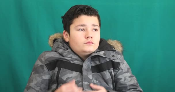Winter portrait of young boy in warm clothes wearing gloves against chroma key green screen background