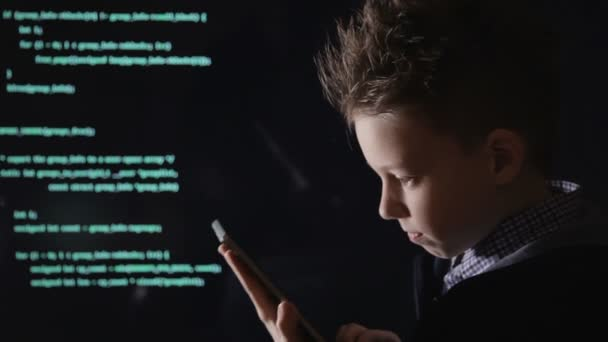 Young schoolboy prodigy - a hacker. Hacker at work. Lots of digits on the computer screen.