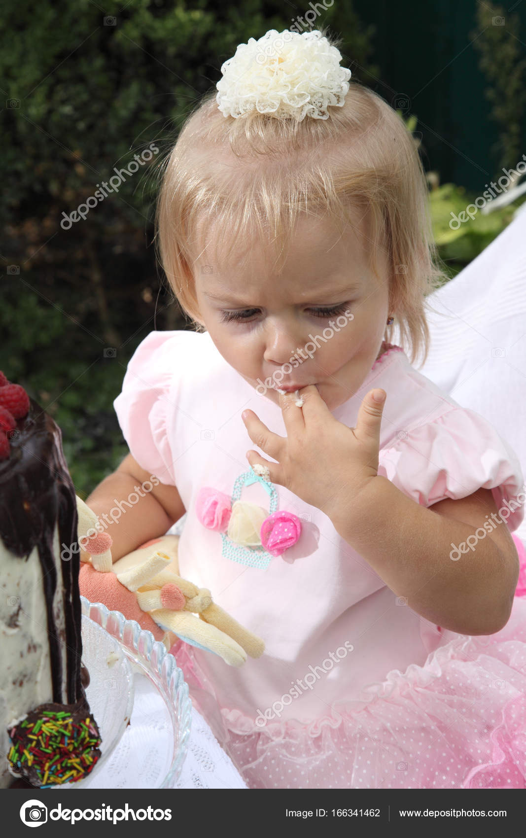 A little girl is trying a birthday cake. Birthday Cake With Candles for  Little Girl — Photo by MastrVideo 6b531e189