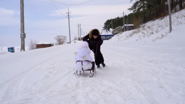 Teen Boy Rodeln Mädchen Kind. Mädchen ist sehr glücklich, dass ihr Bruder rodeln geht. Kinder lieben den Winterspaß. ein bewölkter Wintertag.