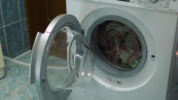 Das Mädchen nimmt die saubere Kleidung aus der Waschmaschine. Tochter hilft ihrer Mutter bei Hausangelegenheiten. Nahaufnahme von Videoaufnahmen.