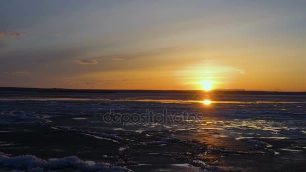 Západ slunce nad velkým rybníkem. Jezero je pokryta volné ledu. LED se pohybuje. Mráčků se vznáší na obloze. Jarní Slunečné večer. Time lapse záběry