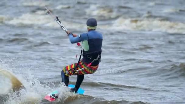 Lassú mozgás: Egy fiatal férfi részt kiteolni. Gyönyörűen korcsolyát a táblán, a hullámok a tó. Erős szél fúj. Ember szereti, a szélsőséges időjárási kiteolni. Hideg őszi Időjárás