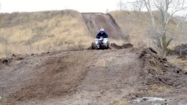 Slow  motion: Sportmen man riding a dirt bumpy road on an ATV. Man practicing and honing their driving skills on ATV over rough terrain. Overcast autumn cold day.