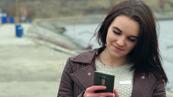 Portrét mladé dívky, krásné dlouhé hnědé vlasy. Dívka vypadá prostřednictvím zpráv na smartphone. Zamračený podzimní den na pláži