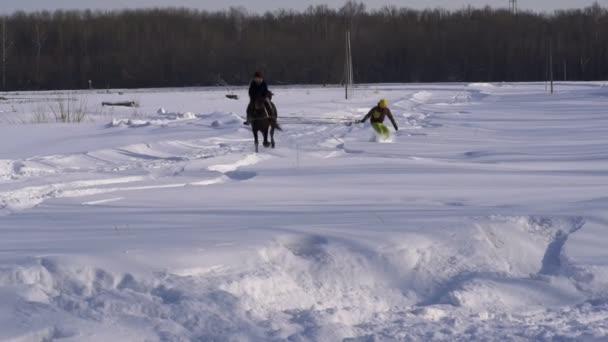 Zeitlupe: Ein Mädchen auf einem Pferd im Galopp Galopp. Ein Pferd ist einen Snowboarder Kerl an einem Seil ziehen. Ein Snowboarder reitet auf einem Snowboard in Schneeverwehungen. Mädchen jockey und Snowboarder Zug paarweise Kerl. Einem sonnigen Wintertag