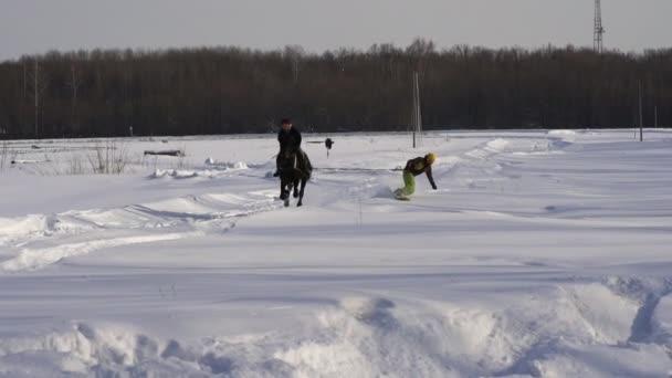 Zeitlupe: Ein Mädchen galoppiert auf einem Pferd im Galopp. Ein Pferd zerrt einen Snowboarder an einem Seil. ein Snowboarder fährt auf einem Snowboard in Schneewehen. Jockey und Snowboarder trainieren paarweise. Ein sonniger Wintertag.