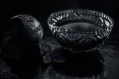 Detoxikační cukrová řepa extrahovaná tinktura ve skleněné misce na černém lesklém povrchu s čerstvě nakrájenou řepou kořenovou zeleninou, která se používá jako prostředek proti zánětu v ledvinách. Vodorovný záběr.