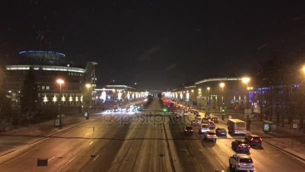 Rusko, Petrohrad, 15 prosinec 2017. Vánoce, zimní atmosféru na ulici, padající sníh, sloupy a domy zdobí různé girlandy, tma, pohyb vozidel na pruhy