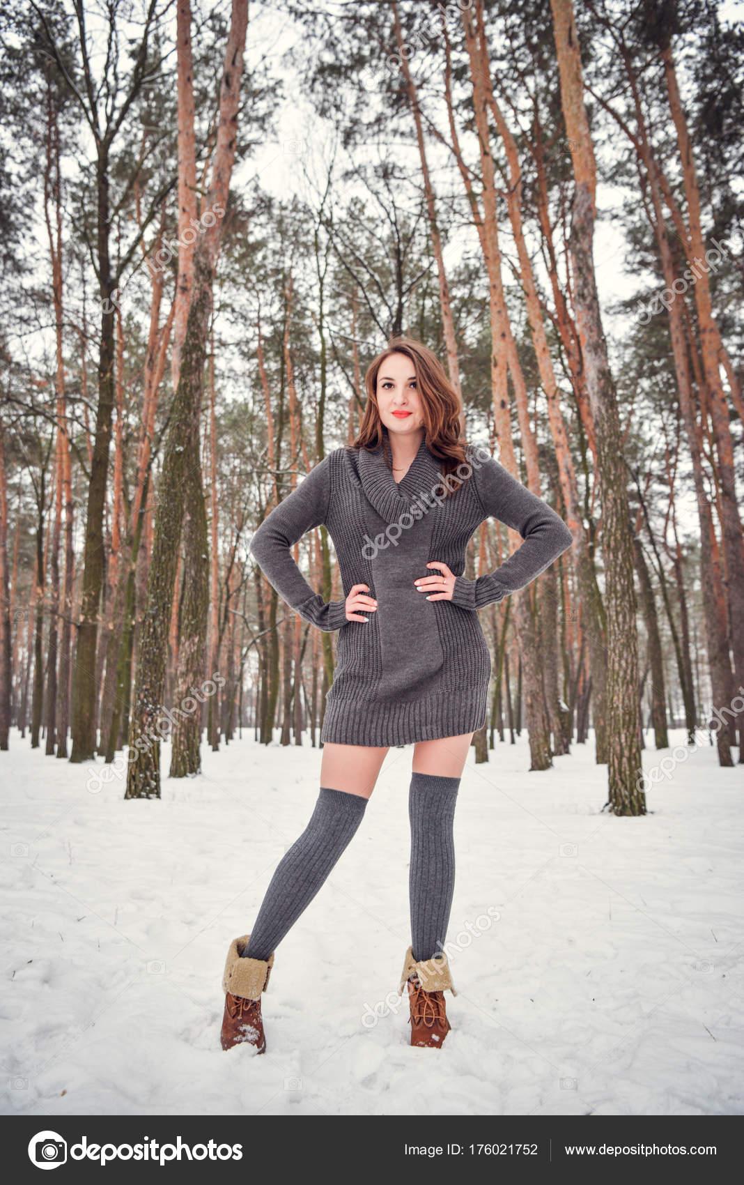 1c8c7e5dc1ad Zimní portrét šťastné krásné dívky s hnědými vlasy v lese zimní sníh. Žena  nosí vysoké ponožky pletené šedé svetr šaty a punčochy.