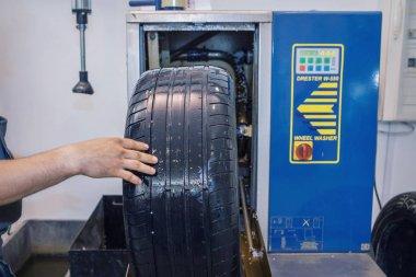 advertising BMW cars, Moscow, 1.11.2018: car repair: wheel replacement closeup. mechanic screwing or unscrewing car wheel at car service garage