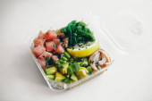 Japán konyha: hal, citrom, hagyma, avokádó egy műanyag tartályban. A hagyományos keleti konyha reklámkoncepciója