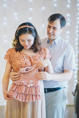 loving couple embracing and tockings considers children's clothes. Healthy lifestyle concept, IVF fashion for pregnant women, children. A man and a woman look into each other's eyes. Husband hugs preg