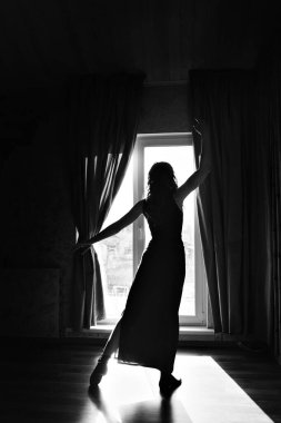 silhouette of a dancing girl at the window. A woman in the light. The concept of strengthening the female body, grace, sport, beauty, style