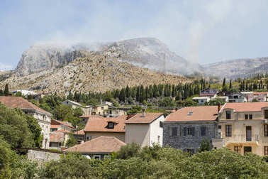 View of the historic old town of Mostar with the mountains in the background where a forest fire rages