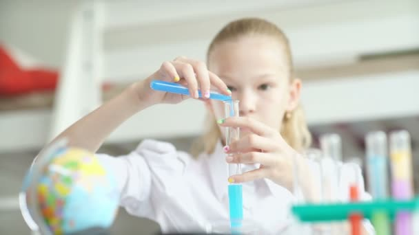 School-age girl pours blue liquid from the flask. Chemistry experiment