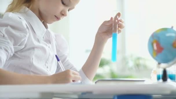 Ragazza seduta a una scrivania e che scrive qualcosa. Scolaretta.