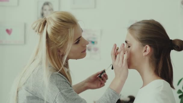 Makeup artist applies eye shadow to model. Make-up work