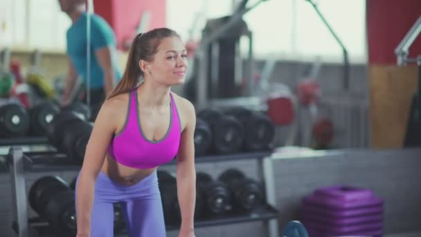 Young women training in the gym: woman smiles and tilts makes the pole