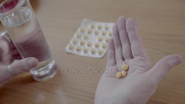 Close-up of round yellow pills in the palm of mature older person.