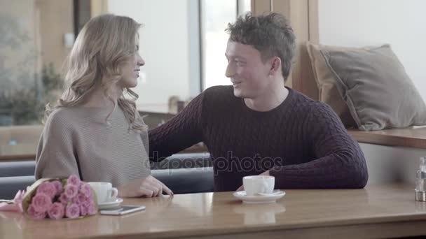 Pár v lásce v kavárně: muž dávat dárky na Valentýna.