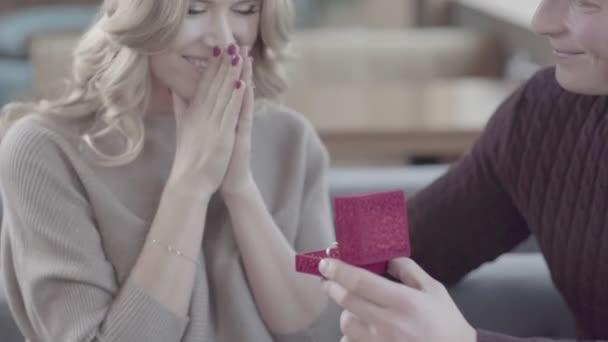 Primo piano di un uomo che tiene una scatola con un anello di nozze. Anello di fidanzamento