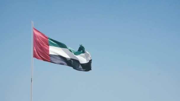 United Arab Emirates flag waving against a blue sky.