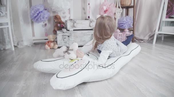 Malá roztomilá dívka si hraje s velkým Plyšová hračka zajíc. Polštář toy
