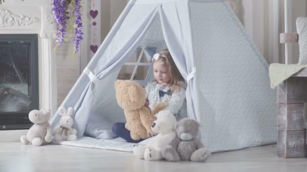 Malá roztomilá holčička s plavými vlasy, sedí obklopen plyšové hračky