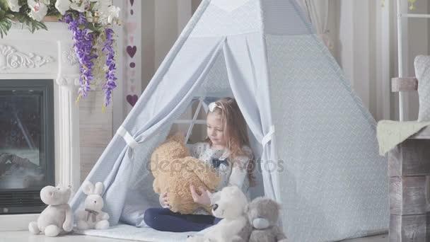 Dívka hází do plyšového medvídka. Malá roztomilá dívka s blond vlasy