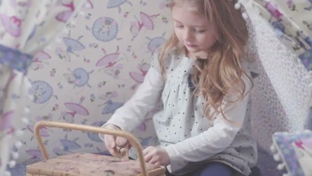 dívka s plavými vlasy hraje v týpí stanu: otevřít skříňku a je překvapen