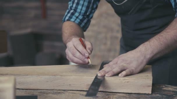 Detail tesaři ruce drží tužku a pravítko.