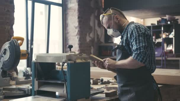 Carpenter cutting wooden board at his workshop. Spread out the tools.