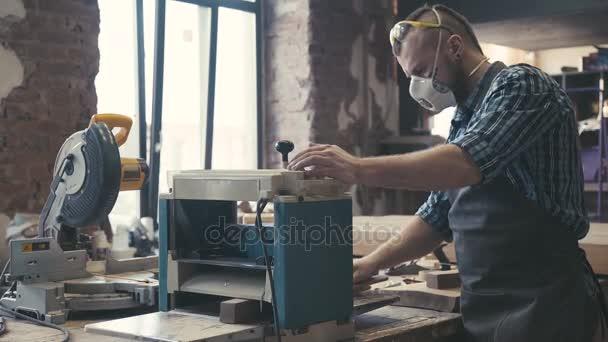 Architekt nebo tesaře pracujícího na prkno dřeva v dílně
