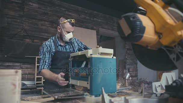 Tesař s dlátem v rukou na workbench