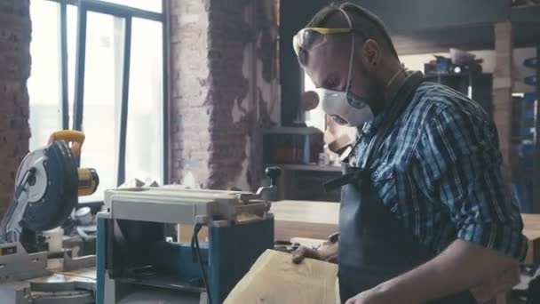 Carpenter with chisel in the hands on the workbench.
