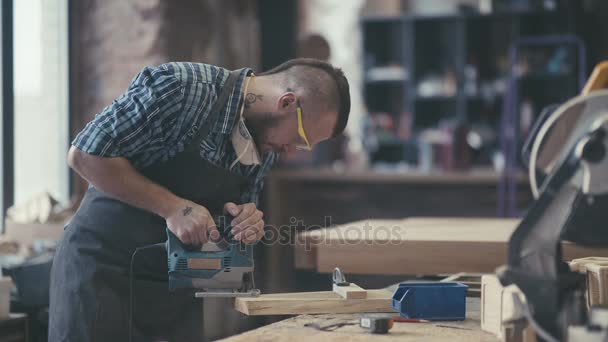 Joiner labouring in mask and glasses for safety. Woodman with tattoo.