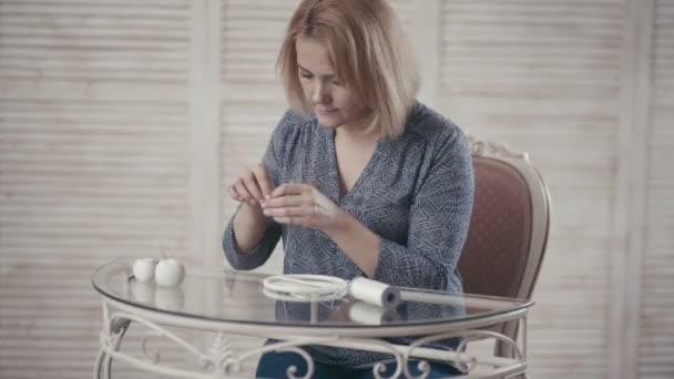 Giovane ragazza seduto al tavolo e fare Dreamcatcher in studio