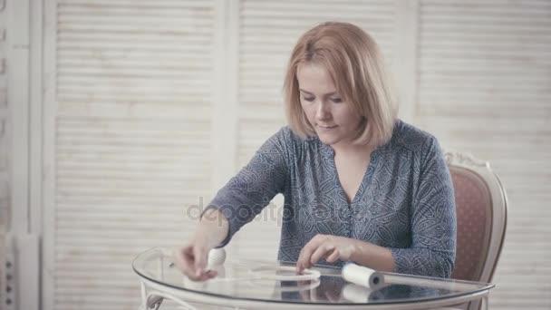 Giovane ragazza seduto al tavolo e fare Dreamcatcher