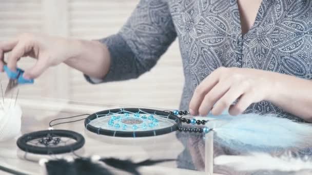 Primo piano delle mani femminili facendo Dreamcatcher di filo nero