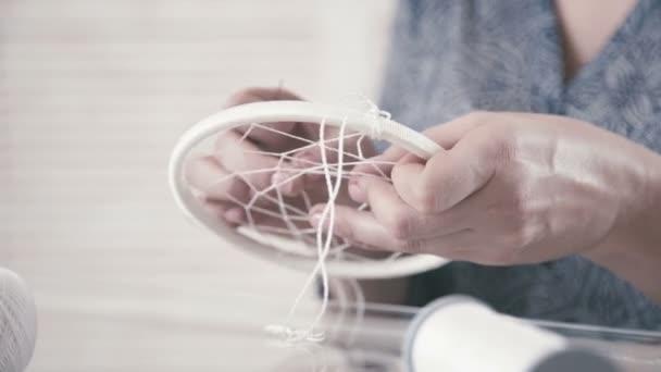 Dreamscatcher da filo, piume e perle di tessitura.