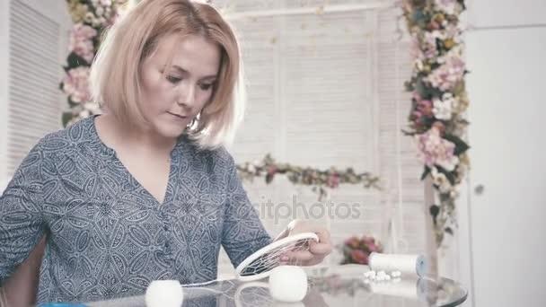 Ragazza che si siede al tavolo e fare decori elemento, attributo