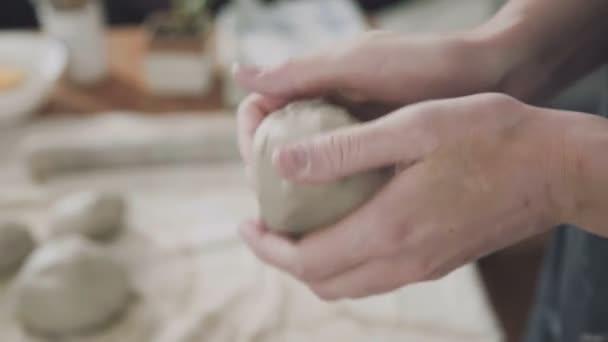Detail: jednorázová bílá hlína v rukou žena keramička