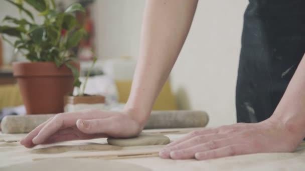Potter žena přejíždí keramik jíl speciální nástroj na stole