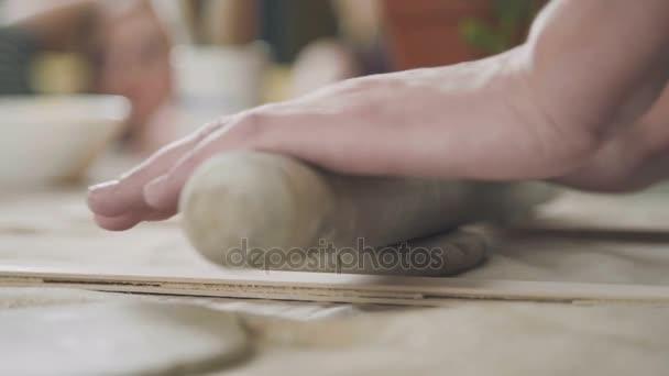 Frau rollt Keramiker Ton Spezialwerkzeug. Frau in der Keramik