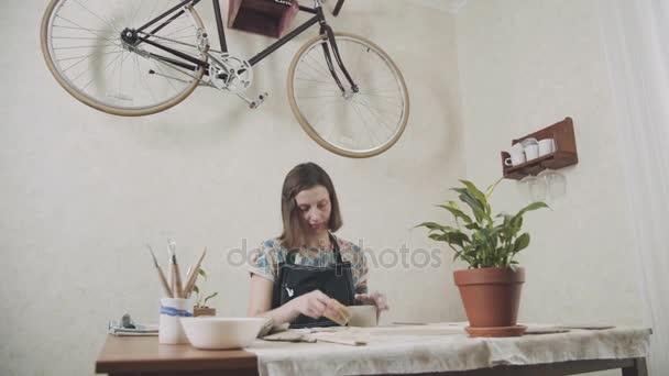 Žena keramička v její umělecké studio se zabývá výrobou hliněných hrnky