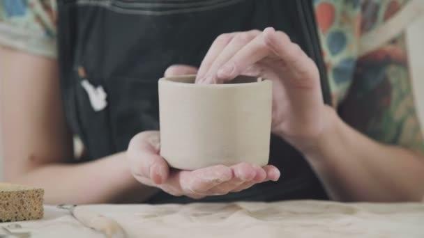 Žena, práce v keramické dílně a dělat hrnek z bílé hlíny